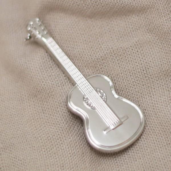 Broche musical con forma de Guitarra Clásica. Cierre con aguja de seguridad.