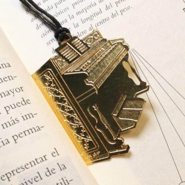 Punto de libro dorado con forma de piano